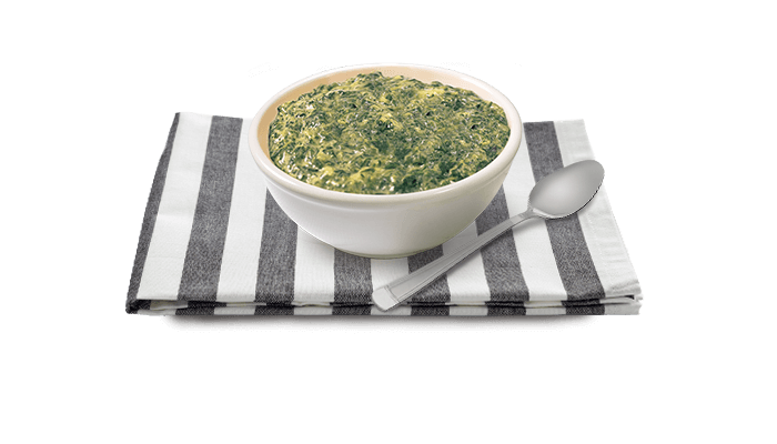 Bowl of Creamed Spinach, with text description, on wooden block table
