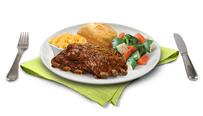 Half rack of ribs on plate with two sides and cornbread loaf, with text description, on wooden block table