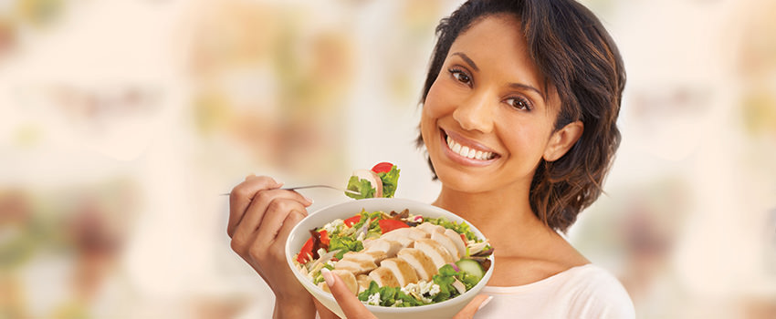 Smiling woman enjoying a Rotisserie Chicken Salad